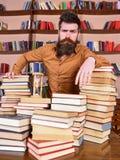 Concetto del bibliotecario L'insegnante o lo studente con la barba sta alla tavola con i libri, defocused Uomo sui supporti premu Fotografia Stock Libera da Diritti