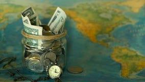 Concetto del bilancio di viaggio Soldi risparmiati per la vacanza in barattolo di vetro sul fondo della mappa di mondo video d archivio