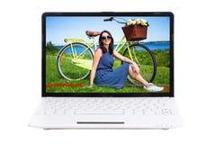 Concetto del blog di viaggio - bella ragazza con la bicicletta sullo scre del computer portatile fotografia stock