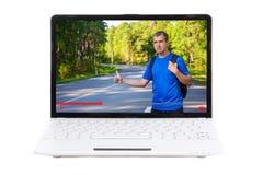 Concetto del blog di viaggio - uomo con lo zaino in video sul ghiaione del computer portatile Fotografia Stock Libera da Diritti