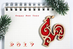 Concetto del buon anno, taccuino con il gallo rosso di legno Fotografia Stock