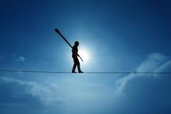 Concetto del camminatore di highline di sfida e di comportamento imprudente in cielo blu Immagine Stock