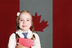 Concetto del Canada con la ragazza felice del bambino in uniforme scolastico con il libro contro i precedenti canadesi della band immagini stock