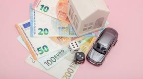 Concetto del casinò, di gioco e di fortuna La casa e l'automobile di modello, giochi tagliano ed euro soldi su fondo rosa con lo  Immagine Stock Libera da Diritti
