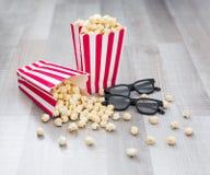 Concetto del cinema - fine su dei vetri 3d e del popcorn in scatole a strisce su fondo di legno fotografia stock libera da diritti