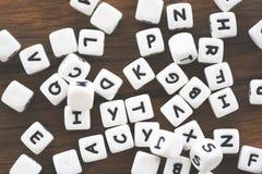 Concetto del cubo dei dadi del testo - la lettera taglia l'alfabeto a cubetti su fondo di legno fotografia stock