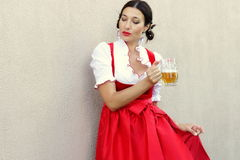Concetto del fest di ottobre Bella donna tedesca in dirndl tipico del vestito più oktoberfest che tiene una tazza di birra di vet Immagine Stock