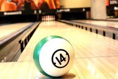 Concetto del gioco con la palla sul pavimento di legno lanciante contro dieci perni Fotografia Stock