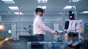 Concetto del gioco di realtà virtuale Il lavoratore ed il robot stringono le mani, mentre accolgono video d archivio
