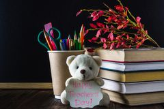 Concetto del giorno dell'insegnante Oggetti su un fondo della lavagna Libri, mela verde, orso con un segno: Il giorno dell'insegn Immagini Stock Libere da Diritti