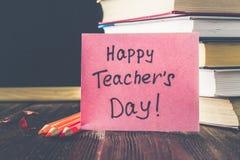 Concetto del giorno dell'insegnante Oggetti su un fondo della lavagna Libri, mela verde, placca: Il giorno, le matite e le penne  Immagine Stock Libera da Diritti