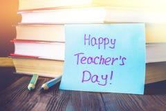Concetto del giorno dell'insegnante Oggetti su un fondo della lavagna Libri, mela verde, placca: Il giorno, le matite e le penne  Fotografie Stock