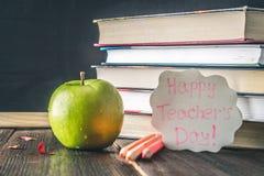 Concetto del giorno dell'insegnante Oggetti su un fondo della lavagna Libri, mela verde, placca: Il giorno, le matite e le penne  Fotografia Stock