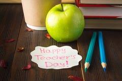Concetto del giorno dell'insegnante Oggetti su un fondo della lavagna Libri, mela verde, placca: Il giorno, le matite e le penne  Fotografia Stock Libera da Diritti