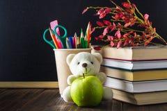 Concetto del giorno dell'insegnante Oggetti su un fondo della lavagna Libri, una mela verde, un orso, matite e penne in un vetro, Fotografia Stock