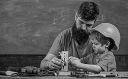 Concetto del lavoro degli uomini Il ragazzo, bambino in casco protettivo fa a mano, riparando, fa i mestieri con il papà Padre co fotografie stock
