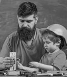 Concetto del lavoro degli uomini Il ragazzo, bambino occupato in casco protettivo fa a mano, riparando, fa i mestieri con il papà fotografia stock