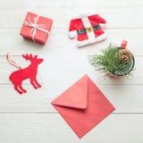 Concetto del messaggio di Natale La carta di carta in bianco bianca con il Natale obietta su fondo di legno bianco Fotografia Stock Libera da Diritti
