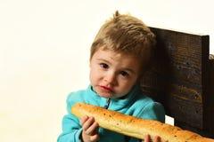 Concetto del negozio del forno Ragazzino con le baguette francesi nel negozio del forno Bambino sveglio con pane fresco nel negoz Fotografia Stock