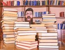 Concetto del nerd L'insegnante o lo studente con la barba indossa gli occhiali, si siede alla tavola con i libri, defocused Uomo, fotografia stock