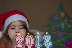 Concetto 2018 del nuovo anno Bambina graziosa in un cappello di Santa Claus che spegne le candele - colpo del primo piano Fotografia Stock Libera da Diritti