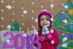 Concetto 2018 del nuovo anno Bella piccola ragazza che decora il numero del nuovo anno fondo di un albero di Natale dipinto e Immagine Stock