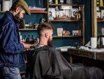 Concetto del parrucchiere Il barbiere con hairdryer scarica i capelli da capo Il cliente barbuto dei pantaloni a vita bassa ha ot fotografie stock libere da diritti