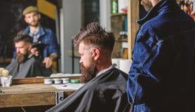 Concetto del parrucchiere L'uomo con la barba coperta di capo nero si siede nella sedia dei parrucchieri, fondo dello specchio Pa immagini stock