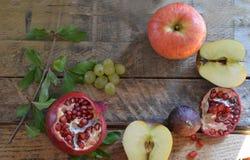 Concetto del raccolto di autunno - frutti sulla tavola di legno Fuoco selettivo Spazio per testo fichi dell'uva del melograno del fotografie stock
