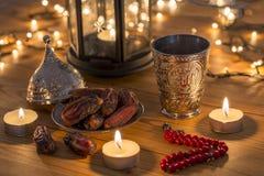 Concetto del Ramadan con le date, il rosario e la tazza dell'acqua del metallo con il testo di Allah in arabo immagini stock libere da diritti