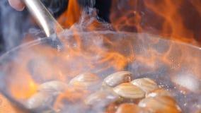 Concetto del ristorante Cottura del piatto fiammeggiato Pasta tradizionale con gamberetto, vongole, cozze Spaghetti da acquolina  archivi video