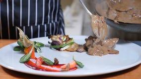 Concetto del ristorante Il cuoco unico in guanti mette le fette di fegato cucinate in salsa crema sulla frutta decorata placcata  archivi video