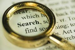 Concetto del ritrovamento e di ricerca con la lente d'ingrandimento dorata del primo piano immagini stock