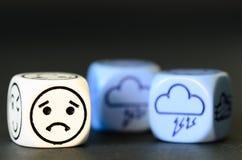 Concetto del tempo triste della tempesta - l'emoticon ed il tempo tagliano su blac Fotografia Stock