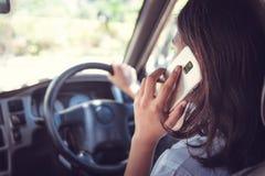 Concetto del veicolo e del trasporto - uomo che per mezzo del telefono mentre conducendo l'automobile fotografia stock