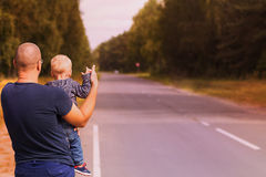 Concetto del viaggio stradale Padre e figlio che provano a fermare l'automobile sulla strada principale La famiglia che fa auto-s Immagine Stock