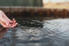 Concetto dell'acqua della natura, mani della donna la ragazza tocca la superficie dell'acqua la ragazza tocca la superficie immagini stock