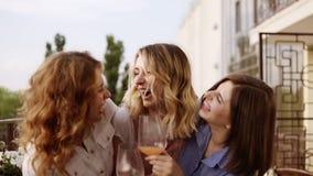 Concetto dell'addio al nubilato Tre belle donne che bevono insieme i cocktail su un terrazzo Donne che chiacchierano e che ridono video d archivio