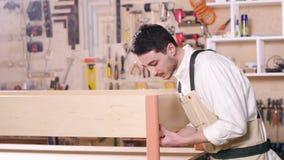 Concetto dell'affare e della fabbricazione Il giovane nell'officina monta la mobilia video d archivio