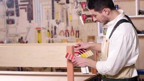 Concetto dell'affare e della fabbricazione Il giovane nell'officina monta la mobilia stock footage