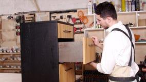 Concetto dell'affare e della fabbricazione Il giovane nell'officina monta la mobilia archivi video