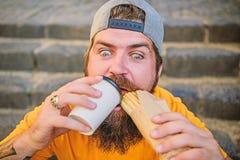 Concetto dell'alimento della via L'uomo barbuto mangia la salsiccia saporita Nutrizione urbana di stile di vita Alimenti industri fotografia stock