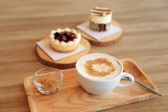 Concetto dell'atmosfera dei confettieri Tazza del caffè caldo del latte fotografia stock libera da diritti