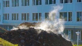 Concetto dell'innovazione delle utilità sotterranee il vapore scoppia della terra L'escavatore scava un foro per determinare stock footage