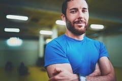 Concetto dell'interno di stile di vita di allenamento Ritratto dell'atleta del giovane che sta con le armi attraversate prima del Fotografia Stock