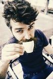 Concetto dell'intervallo per il caffè Tipo che ha resto con il caffè del caffè espresso Pantaloni a vita bassa sul caffè bevente  Fotografie Stock