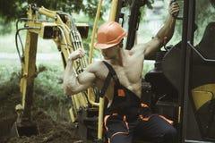 Concetto dell'operaio Bicipite della flessione dell'operaio e muscolo del tricipite Forte operaio alla cabina dell'escavatore Ope immagine stock libera da diritti