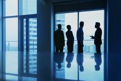 Concetto dell'ufficio con le siluette degli impiegati contro la grande finestra Fotografie Stock