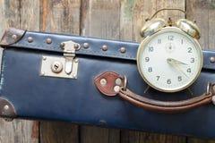 Concetto dell'ultimo minuto di viaggio con la vecchie retro valigia e sveglia Fotografie Stock Libere da Diritti