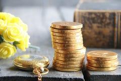 Concetto della Banca Pile di monete dorate e rose sulla tavola d'annata Fotografia Stock